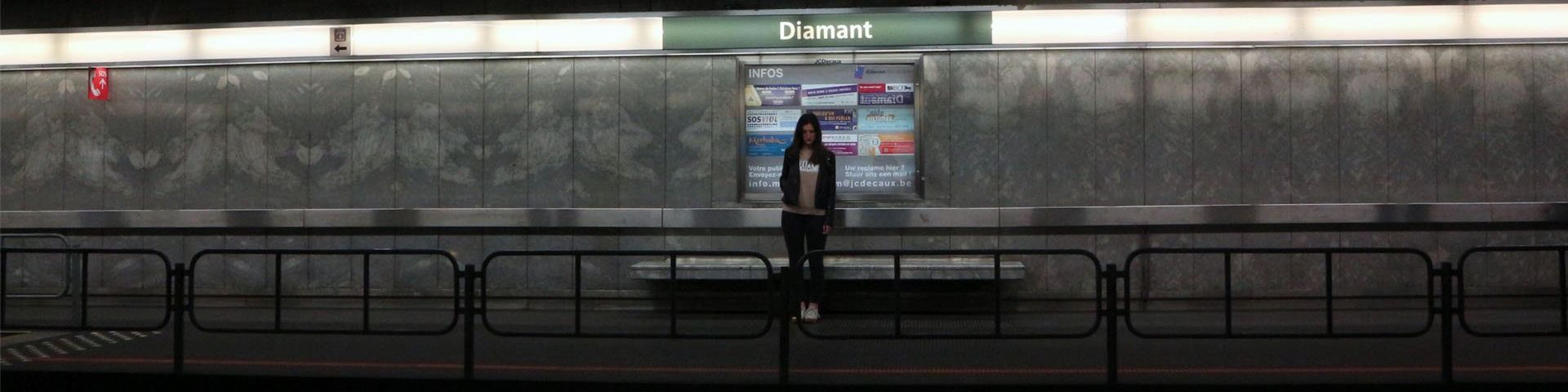 A young woman stands alone on a train platform.